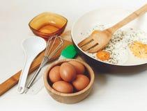 Huevos fritos en el sartén, ingredientes del desayuno, accesorios de la cocina Huevos de Brown frescos en la placa de madera Coci Imagen de archivo