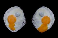 Huevos fritos en fondo negro Foto de archivo libre de regalías