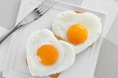 Huevos fritos en forma de corazón Imágenes de archivo libres de regalías