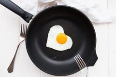 Huevos fritos en forma de corazón en una cacerola negra Fotografía de archivo libre de regalías