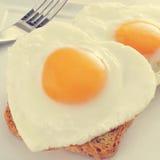 Huevos fritos en forma de corazón, con un efecto del filtro Fotografía de archivo