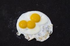 Huevos fritos en la calzada del asfalto foto de archivo