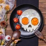 Huevos fritos en la forma de un cráneo y de tomates frescos Desayuno en las decoraciones de Halloween Imágenes de archivo libres de regalías