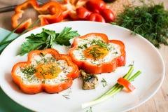 Huevos fritos en pimienta e hierbas en la placa Fotografía de archivo libre de regalías