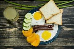 Huevos fritos en placa con los tomates, las salchichas y el pan de cereza para el desayuno foto de archivo