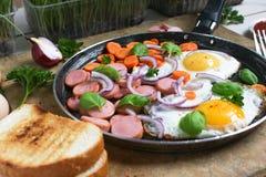 Huevos fritos en un sartén con las verduras foto de archivo