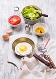 Huevos fritos en un sartén con los tomates y la ensalada vegetal para el desayuno Foto de archivo