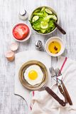 Huevos fritos en un sartén con los tomates y la ensalada vegetal para el desayuno Imagenes de archivo