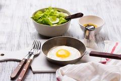 Huevos fritos en un sartén con los tomates y la ensalada vegetal para el desayuno Fotos de archivo libres de regalías