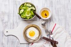 Huevos fritos en un sartén con los tomates y la ensalada vegetal para el desayuno Fotografía de archivo