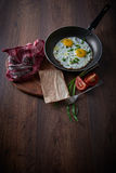 Huevos fritos en un sartén Con los tomates y las cebollas verdes En una tabla de cortar, y en un fondo oscuro Desayuno sano imagenes de archivo