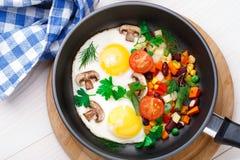 Huevos fritos en una cacerola con las verduras Imagen de archivo