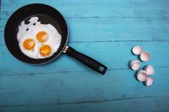 Huevos fritos en una tabla de madera fotos de archivo