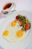 Huevos fritos para el desayuno con los tomates y los pepinos frescos Foto de archivo