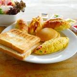 Huevos fritos, tocino, salchichas, desayuno y ensalada fresca para la salud fotos de archivo
