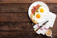 Huevos fritos, tocino y pan italiano del ciabatta en la placa blanca Taza de café Opinión superior del desayuno Fondo de madera fotos de archivo