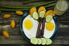 Huevos fritos y salchicha en una placa azul de la porcelana foto de archivo