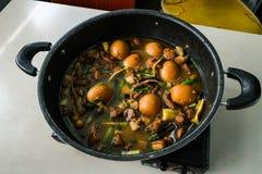 Huevos guisados en un pote colocado en la tabla fotos de archivo