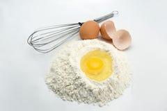 Huevos, harina y herramientas de la cocina Foto de archivo
