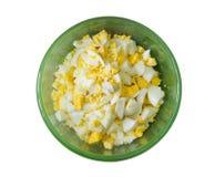 Huevos hervidos cortados en trozos pequeños en un cuenco verde aislado en el fondo blanco Foto de archivo