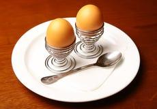 Huevos hervidos en una placa blanca con una cuchara Imagenes de archivo