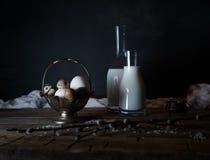 Huevos, leche y mantequilla orgánicos frescos, aún vida en el estilo rústico, fondo de madera del vintage Foto de archivo