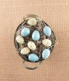 Huevos manchados acurrucados en cesta Foto de archivo libre de regalías