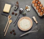 Huevos, mantequilla y harina, un sistema de las herramientas para amasar la pasta, en un gris fotos de archivo