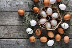 Huevos marrones del pollo fresco en cartón en fondo de madera rústico Foto de archivo libre de regalías