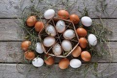 Huevos marrones del pollo fresco en cartón en fondo de madera rústico Imagen de archivo