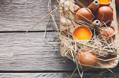 Huevos marrones del pollo fresco en cartón en fondo de madera rústico Fotos de archivo