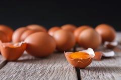 Huevos marrones del pollo fresco en la madera rústica en el fondo negro Foto de archivo