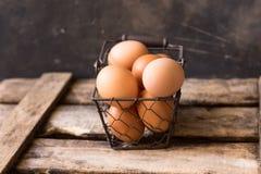 Huevos marrones frescos en una cesta de alambre en una caja de madera del vintage, fondo negro, Pascua, decoración Fotografía de archivo libre de regalías
