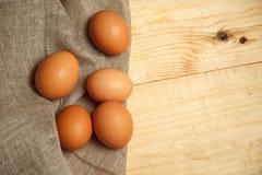 Huevos marrones orgánicos crudos sobre la servilleta de lino y el fondo de madera rústico Imágenes de archivo libres de regalías