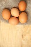 Huevos marrones orgánicos crudos sobre la servilleta de lino y el fondo de madera rústico Imagen de archivo