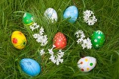 Huevos multicolores en fondo de la hierba verde Imagen de archivo