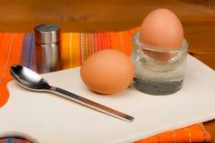 2 huevos pasados por agua en un tablero de madera Imágenes de archivo libres de regalías