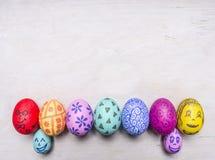 Huevos pintados brillantes, coloridos para Pascua, en fila lugar presentado de la frontera para el cierre rústico de madera de la Foto de archivo