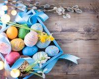 Huevos pintados coloridos de Pascua con las flores de la primavera Imagen de archivo libre de regalías