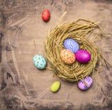 Huevos pintados para el cierre rústico de madera de la opinión superior del fondo de la jerarquía de Pascua para arriba Foto de archivo