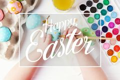 Huevos, pinturas y cepillos hervidos pintados a mano de Pascua del niño en una tabla blanca Preparación para el día de fiesta Las foto de archivo libre de regalías