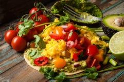 Huevos Rancheros. Home made huevos rancheros. A popular Mexican breakfast dish of eggs, tomato, avocado and chili peppers served on a corn tortilla Royalty Free Stock Image