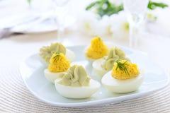 Huevos rellenos con crema batida del queso y del aguacate en la tabla festiva Fotos de archivo