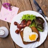 Huevos revueltos con la salchicha en forma de corazón para el desayuno Foto de archivo