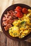 Huevos revueltos con las cebolletas, el tocino y el primer de los tomates Vertica Imágenes de archivo libres de regalías