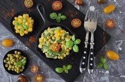 Huevos revueltos con las habas verdes, el maíz, los guisantes verdes y la albahaca fresca Foto de archivo libre de regalías