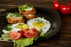 Huevos revueltos con las hierbas y los tomates frescos Foto de archivo