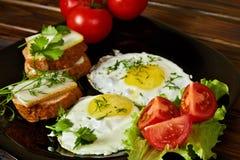 Huevos revueltos con las hierbas y los tomates frescos Imágenes de archivo libres de regalías