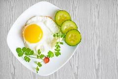 Huevos revueltos con los pepinos y los tomates en la placa en la tabla de madera, Imagenes de archivo