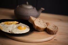 Huevos revueltos con pan de centeno en una tabla de madera Tetera de cerámica japonesa en el fondo Comida de las fotos en a Fotos de archivo libres de regalías